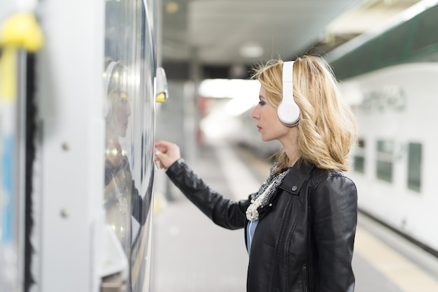 Woman taking a soda from an automatic machine