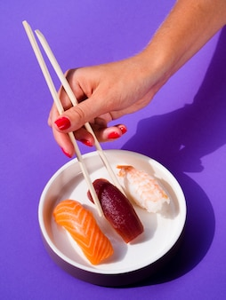Woman taking a sushi from sushi plate with chopsticks