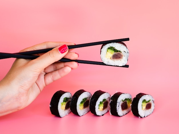 Woman taking a sushi roll with chopsticks