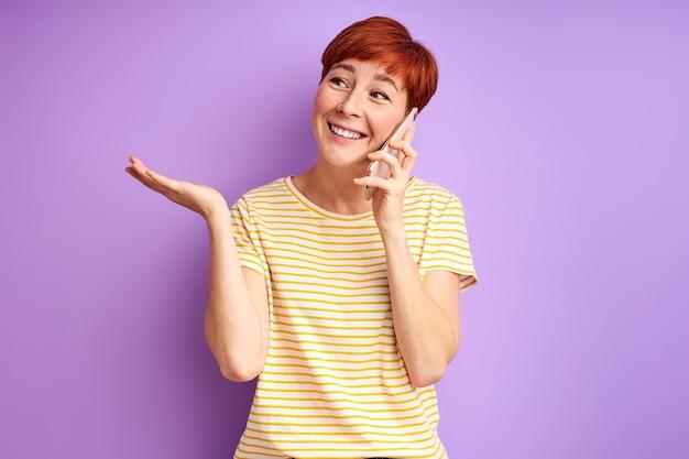 紫色の壁に隔離された友人とニュースを共有する電話で話す女性