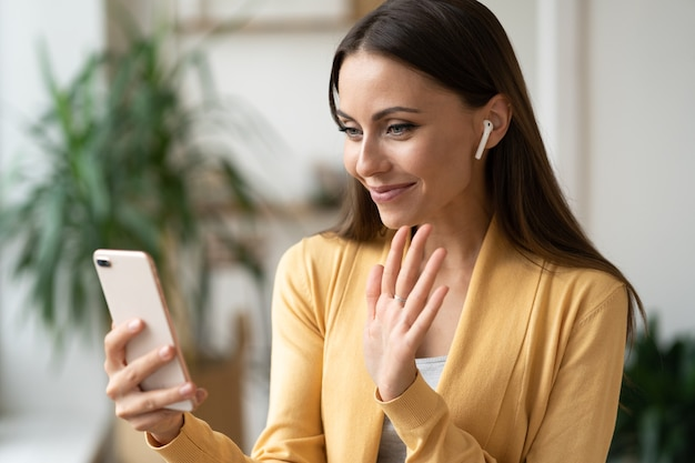 Woman talk on video phone call with smartphone and wireless headphones wave hand to camera greeting
