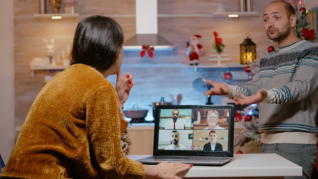 Woman talking to business people on video call conference