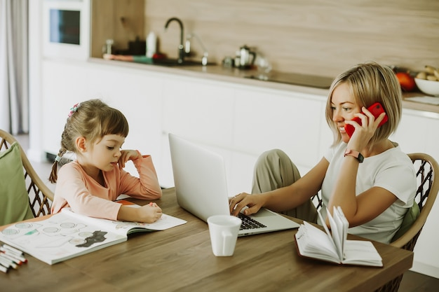 Woman talking by phone while working at home and her little daughter sitting near and drawing