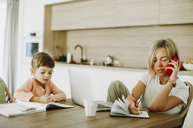 Woman talking by phone and writing notes while working at home her daughter sitting next to her