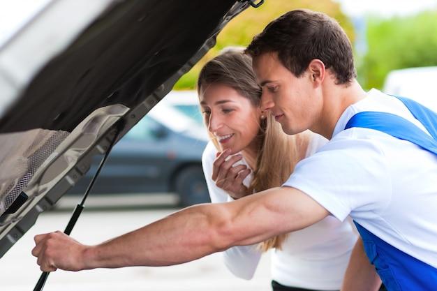 Woman talking to car mechanic in repair shop