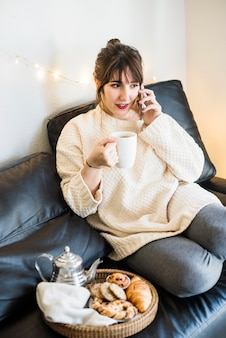 Woman talking on cellphone holding cup of coffee