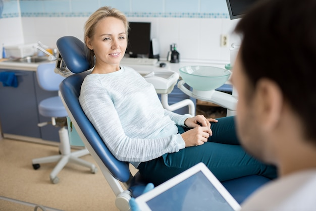 Woman talking to dentist in cabinet