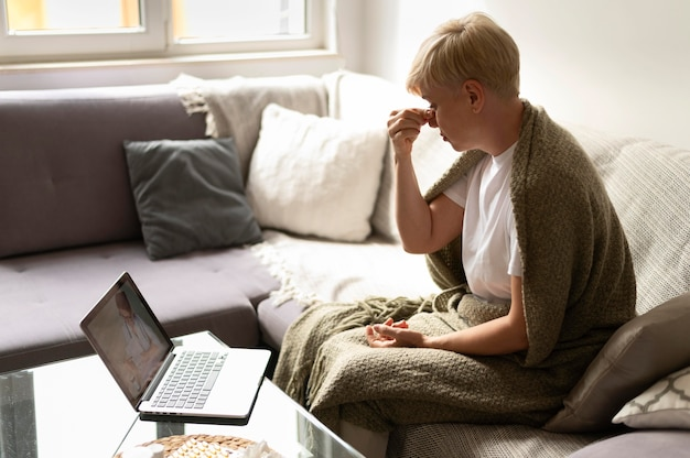 Woman talking to doctor online medium shot