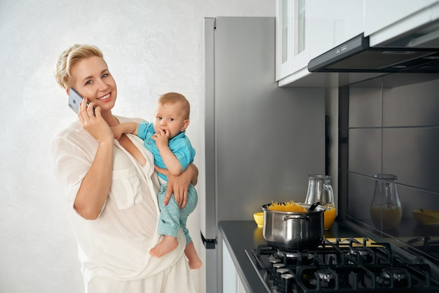 Woman talking on mobile cooking dish and carrying baby