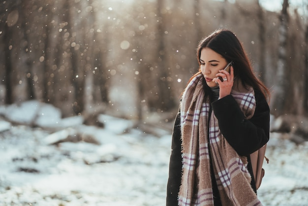 Woman talking on mobile phone. smiling woman talking on mobile phone in cold winter day.