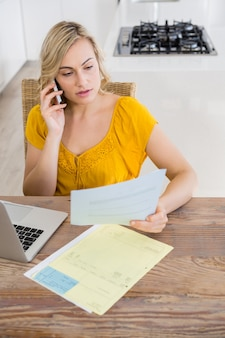 Woman talking on mobile phone while looking at bill in kitchen