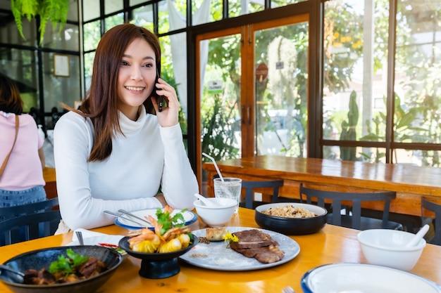 레스토랑에서 휴대 전화 통화하는 여자