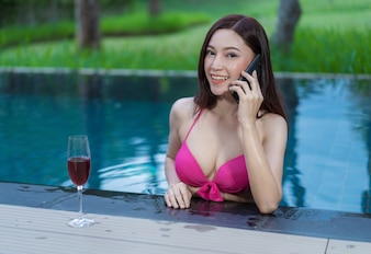 Woman talking on a mobile phone in swimming pool