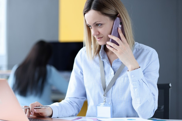 Женщина разговаривает по мобильному телефону и смотрит на ноутбук