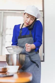 金属製のボウルに小麦粉をふるいながら携帯電話で話している女性。