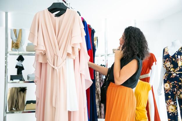 옷을 선택하고 패션 매장에서 선반에 드레스를 검색하는 동안 셀에 얘기하는 여자. 중간 샷, 측면보기. 부티크 고객 또는 소매 개념