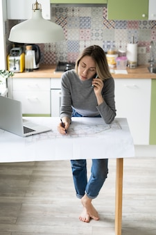 Женщина разговаривает по мобильному телефону, обсуждает детали архитектурного проекта, делает заметки на чертеже