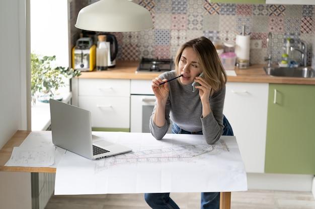 Женщина разговаривает по мобильному телефону, обсуждает с коллегой детали архитектурного проекта или чертежа