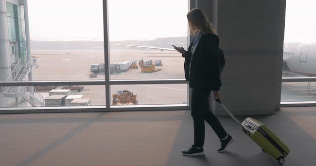 Женщина разговаривает по мобильному телефону в терминале аэропорта