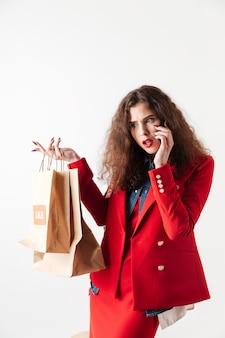 Женщина разговаривает по мобильному телефону и держит бумажные сумки