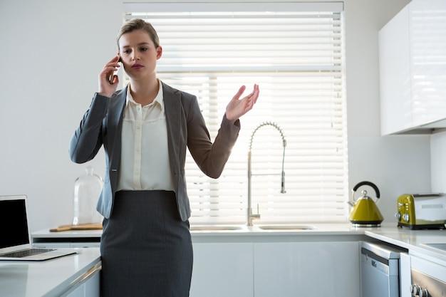 Женщина разговаривает по мобильному телефону на кухне