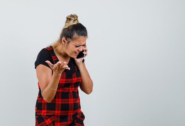 Женщина разговаривает по мобильному телефону в платье-сарафане и нервничает, вид спереди.