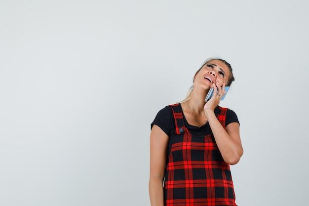 Женщина разговаривает по мобильному телефону в платье-сарафане и смотрит задумчиво. передний план.