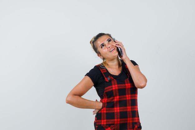 Женщина разговаривает по мобильному телефону в платье-сарафане и смотрит задумчиво, вид спереди.