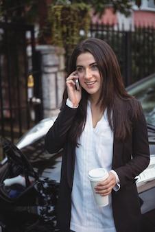 車の充電中に携帯電話で話している女性