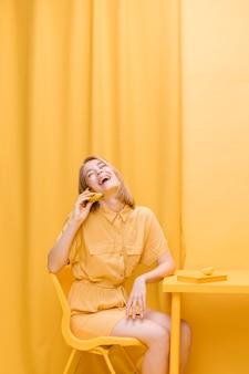 노란색 장면에서 전화 통화하는 여자