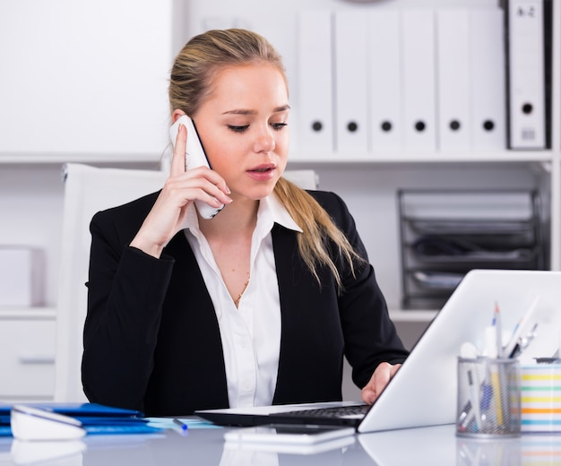 Женщина разговаривает по телефону в офисе