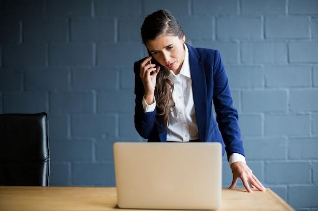 사무실에서 노트북을 사용하는 동안 전화 통화하는 여자