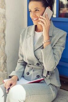 Женщина разговаривает по смартфону.