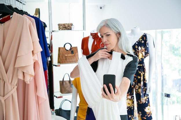 ファッション店でスマートフォンで話し、ドレスを見せている女性。ミディアムショット。ブティックの顧客またはコミュニケーションの概念