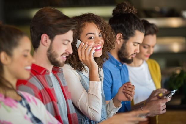 Женщина разговаривает по смартфону, пока друзья используют мобильный телефон
