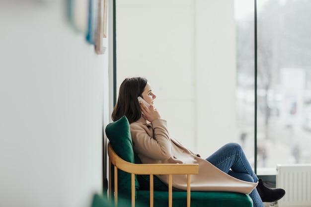電話で話し、カフェに座っている女性