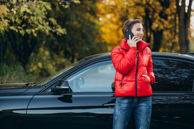 電話で話し、車のそばに立っている女性