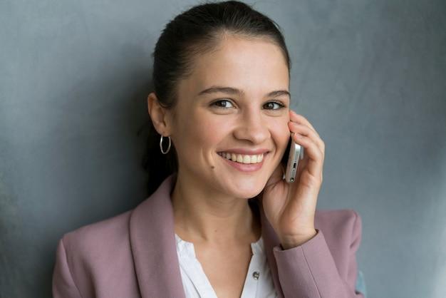 Женщина разговаривает по телефону дома