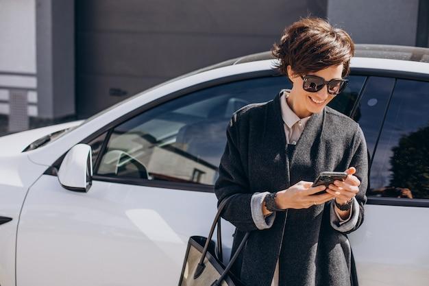 車のそばで電話で話している女性