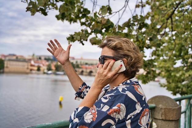 川の近くの電話で話している女性
