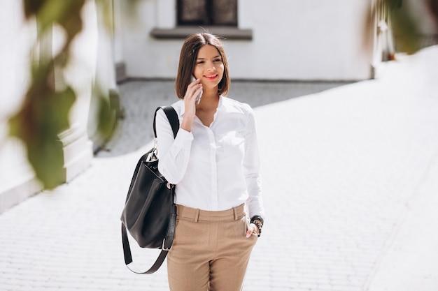 Женщина разговаривает по телефону на улице города
