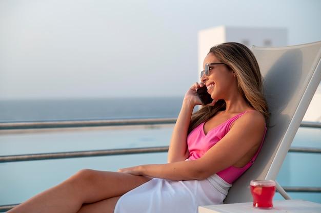 プールサイドでリラックスしながら電話で話している女性