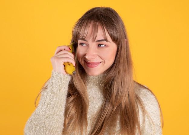 Женщина разговаривает по телефону с бананом