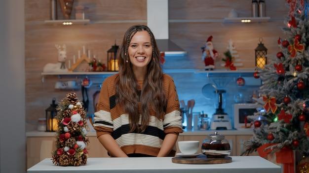 自宅の装飾されたキッチンでビデオ通話で話している女性