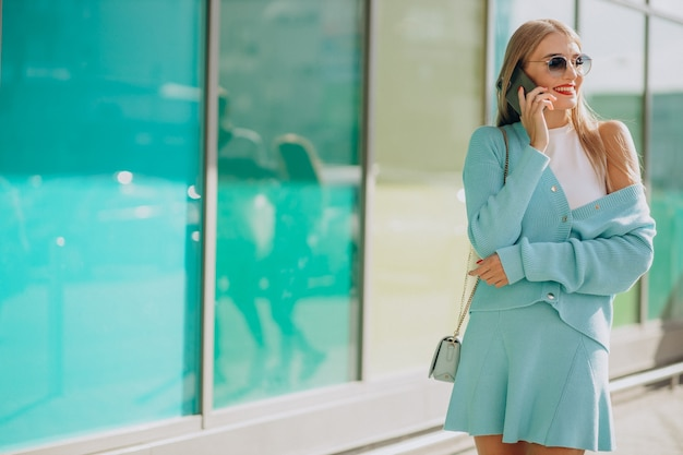 Woman talking on the phone by shopping mall