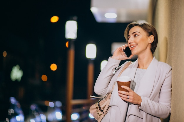 Woman talking on phone and drinking coffee outside in the street at night