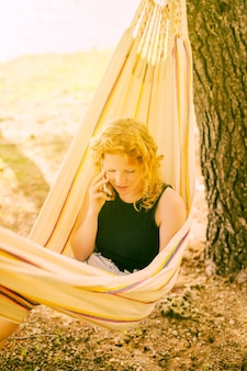 Woman talking on phone in hammock