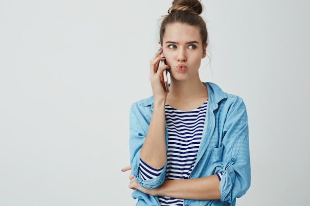 Woman talking phone hearing hot fresh rumours gossiping excited intrigued, listening interesting news holding smartphone pressed ear folding lips interested looking aside, standing