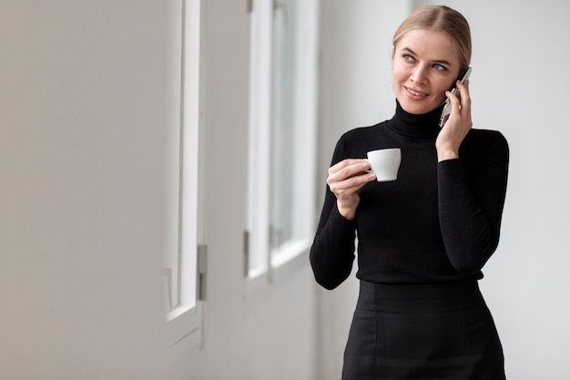 Woman talking at phone and holding cup of coffee