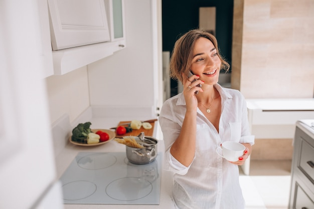 Woman talking on the phone at kitchen and cooking breakfast